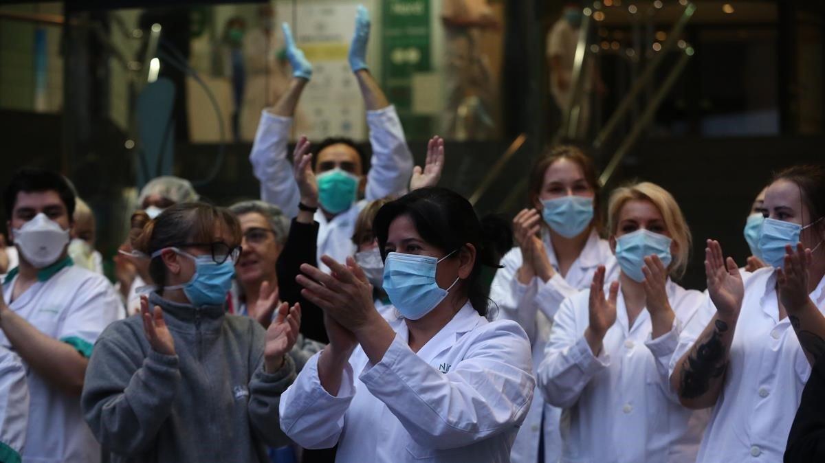 Sanitarios reciben el aplauso de la gente en la puerta del Hospital Clínic de Barcelona, ayer.