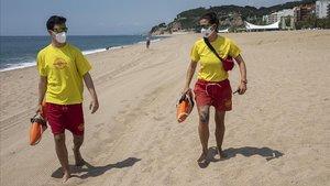 Dos socorristas de Proactiva, con las mascarillas en una playa de Calella, ayer.