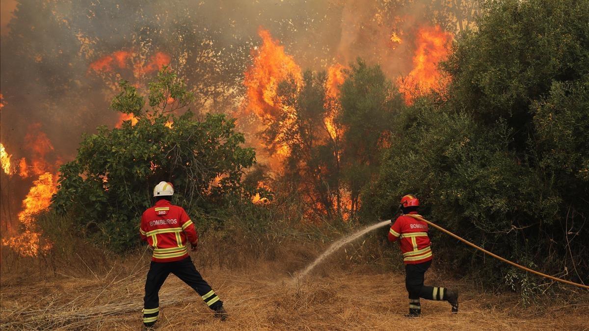 Bomberos tratan de extinguir las llamas del incendio que arrasa el Algarve portugués, este martes.