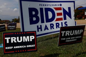 Campaign signs for U.S. Democratic presidential candidate Joe Biden and Vice presidential candidate Kamala Harris stand with signs for U.S. President Donald Trump on a hillside in Monroeville, Pennsylvania, U.S., October 21, 2020. REUTERS/Shannon Stapleton