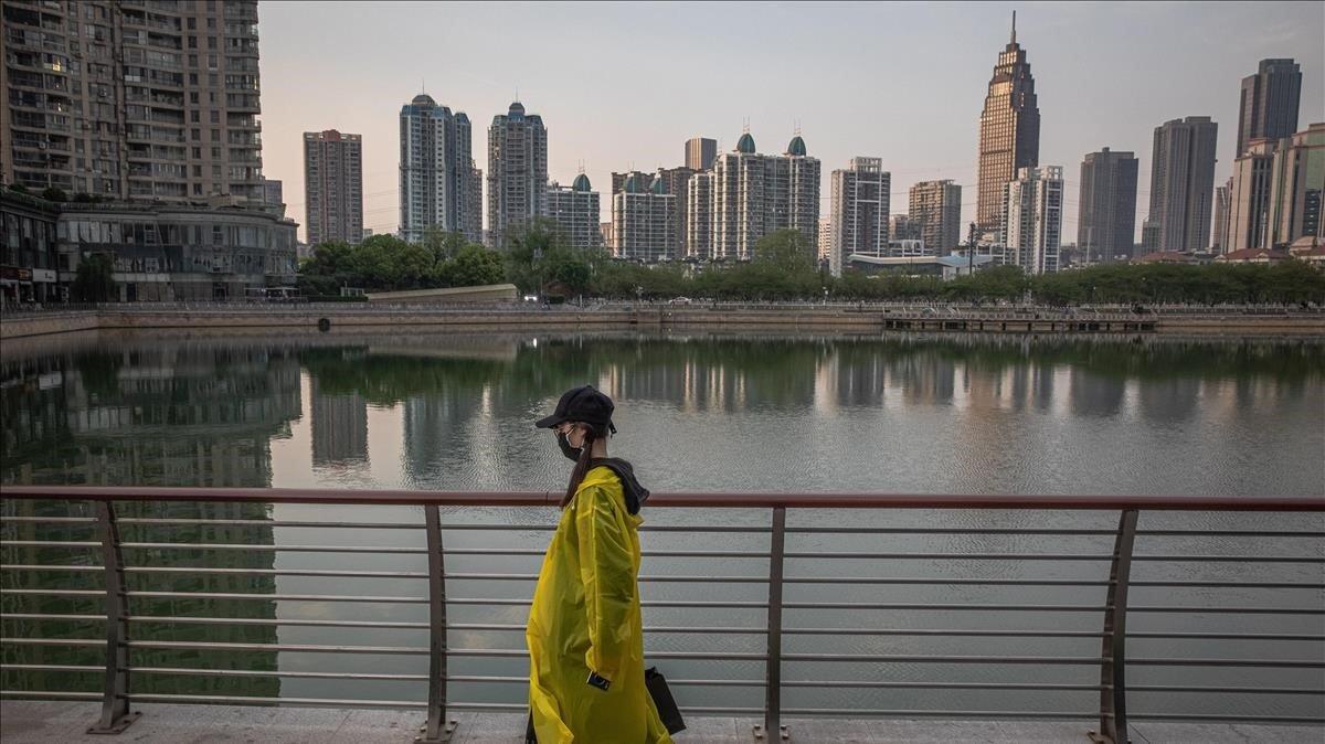 Una mujer camina junto a un lago de Wuhan (China).