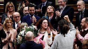 La diputada del grupo de Unidas Podemos Aina Vidal que hoy ha asistido a votar a pesar de estar enferma de cáncer recibe un ramo de flores de sus compañeros al termino de la segunda y definitiva votación