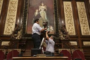 Dos trabajadores municipales retiran el busto del rey Juan Carlos I, en julio.