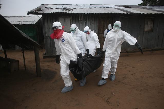 Un equipo médico carga con un cadáver afectado por el ébola en Liberia.