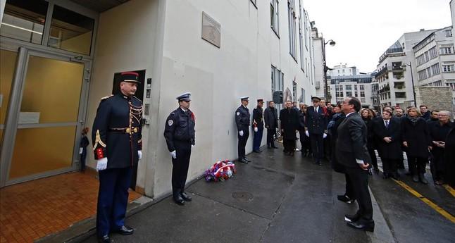 El presidente francés François Hollande observa una placa en conmemoración a las víctimas del ataque terrorista al semanario satírico francésCharlie Hebdo.