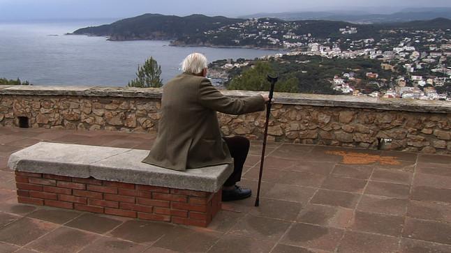 Un jubilado contempla el mar desde un pueblo de la Costa Brava.