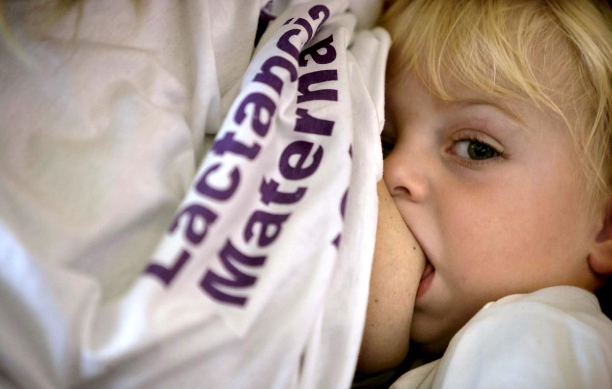 Una mujer da a su hijo el pecho en la tetada pública organizada por la asociación Criar con Apego.