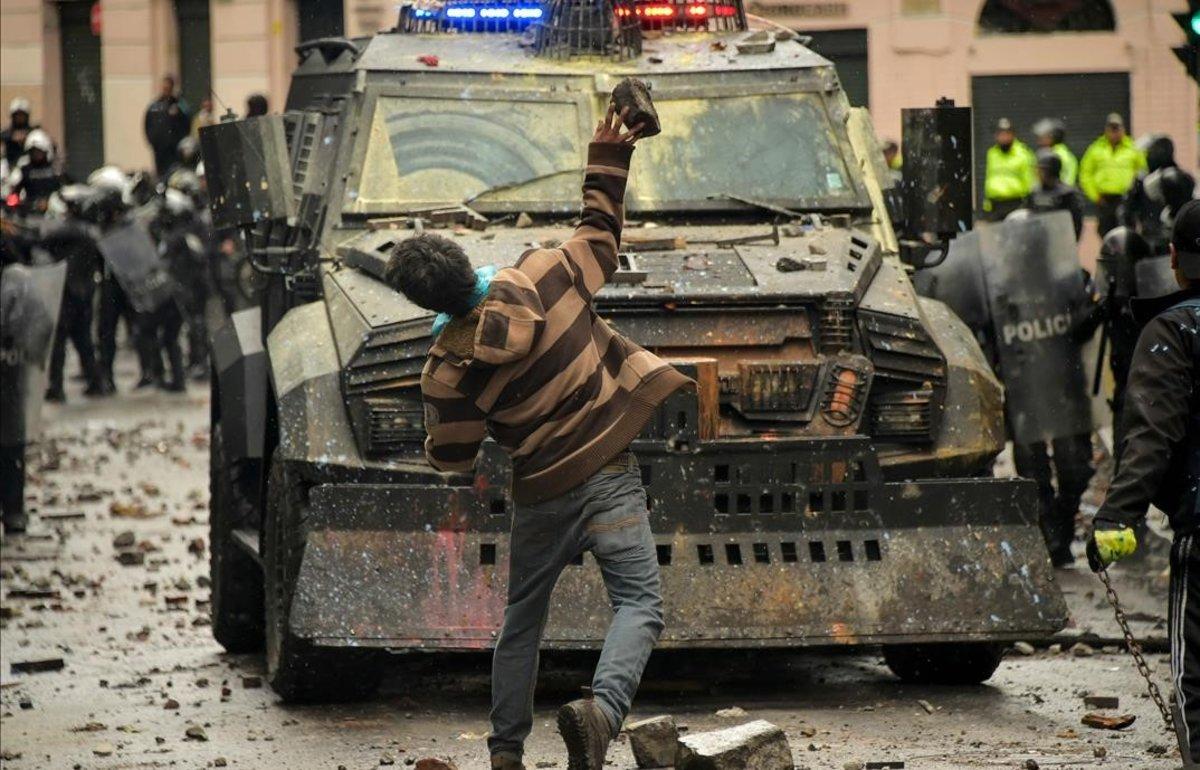 Un manifestante lanza un objeto contra un vehículo policial en una protesta contra el Gobierno de Lenin Moreno, este viernes, en Quito.