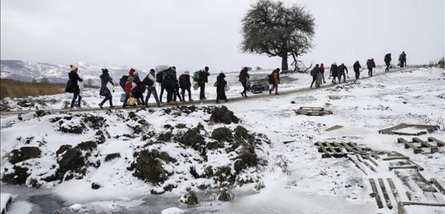 Migrantes caminan en fila tras cruzar la frontera macedonia con Serbia, este lunes.