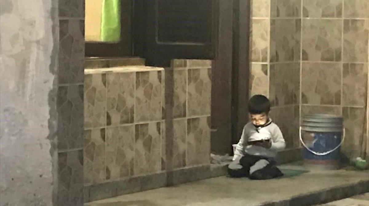Un niño se entretiene con él móvil de su madre a las puertas de su casa de Termas de Río Hondo.