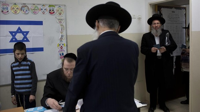 Un niño observa como se disponen a votar varios ultraortodoxos en Bnei Brak.