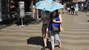 Ola de calor en Barcelona. Una pareja se protege del sol con un paraguas en las Ramblas, el 3 de agosto del 2018