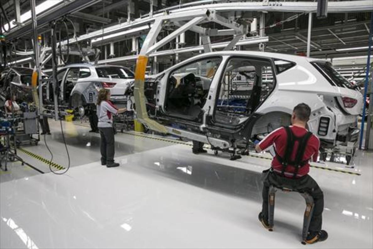 Operarios en una cadena de montaje de una empresa automovilística.