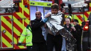 La policía asiste a un hombre herido en el ataque en el Puente de Londres, este viernes.