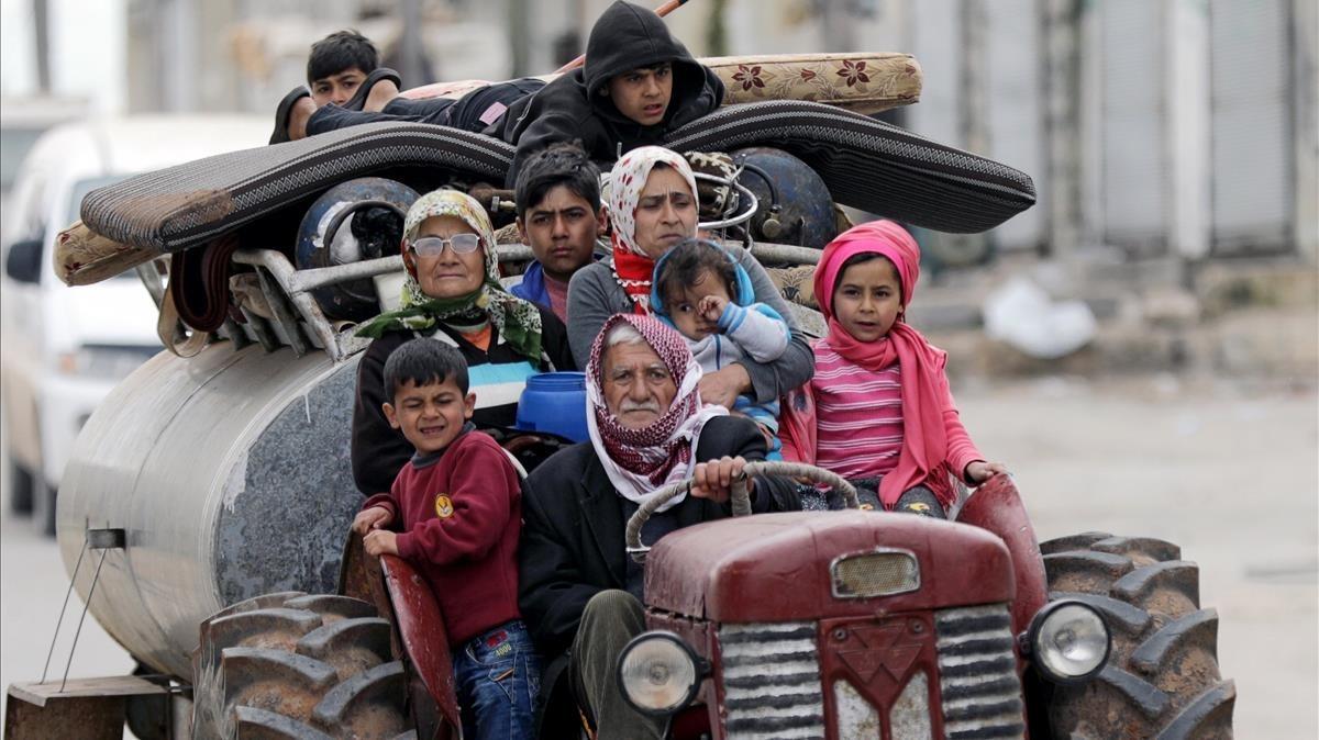 Una familia huye de los combates en la localidad siria deKhaldieh.
