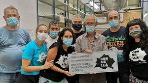 Representantes y voluntarios del Banc d'aliments de Cornellà con representantes de Cornellà Actitud haciendo entrega de la donación para la recaptación solidaria al Corpus 2020.