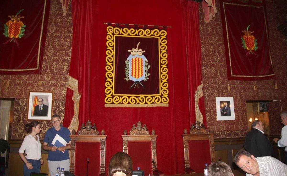El salón de plenos del Ayuntamiento de Tarragona, con el escudo municipal presidiendo el espacio, y los retratos de Quim Torra y Felipe VI.