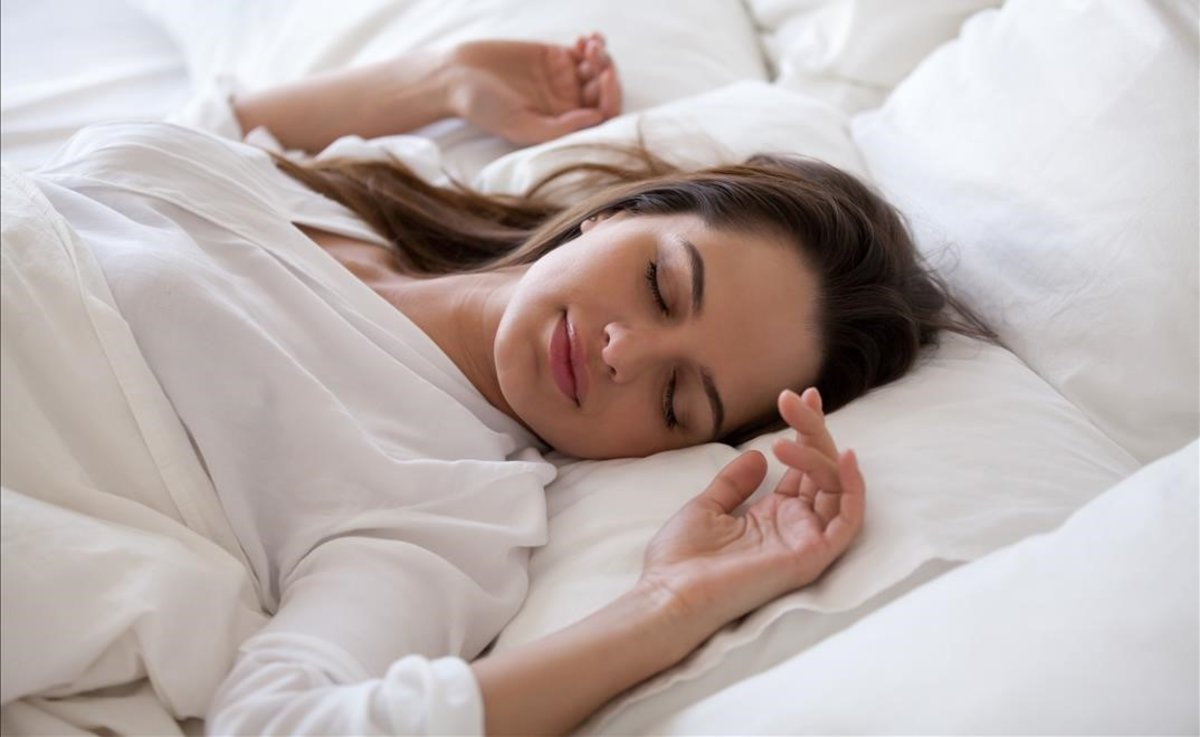 Una chica se despereza en la cama.