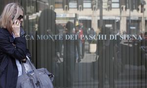 Una mujerpasa ante una oficina del banco Monte Dei Paschi Di Siena en Roma.
