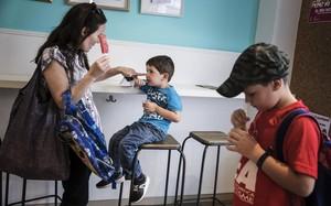 Una mujer y sus dos hijos saborean un helado en una heladería de Santa Coloma, el viernes.