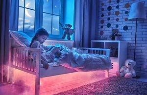 Una niña en su cama con su amigo imaginario.