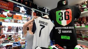 Una vendedora coloca una camiseta de Cristiano con el 7 de la Juventus.