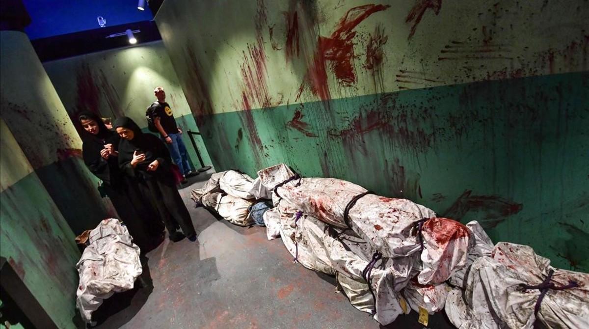 Unas mujeres exploran un pasillo entre cadáveres amortajados