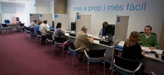 Varias personas tramitan su declaración del IRPF en una delegación de Hacienda en Barcelona.