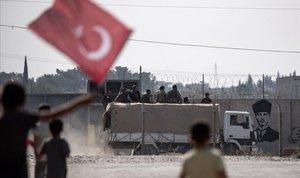 Varios niños ondean la bandera turca mientras saludan a los soldados sirios apoyados por Ankara que se dirigen al norte de Siria.
