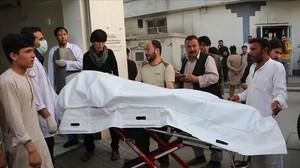 Voluntarios afganos trasladan un cuerpo en una camilla hacia el hospital.