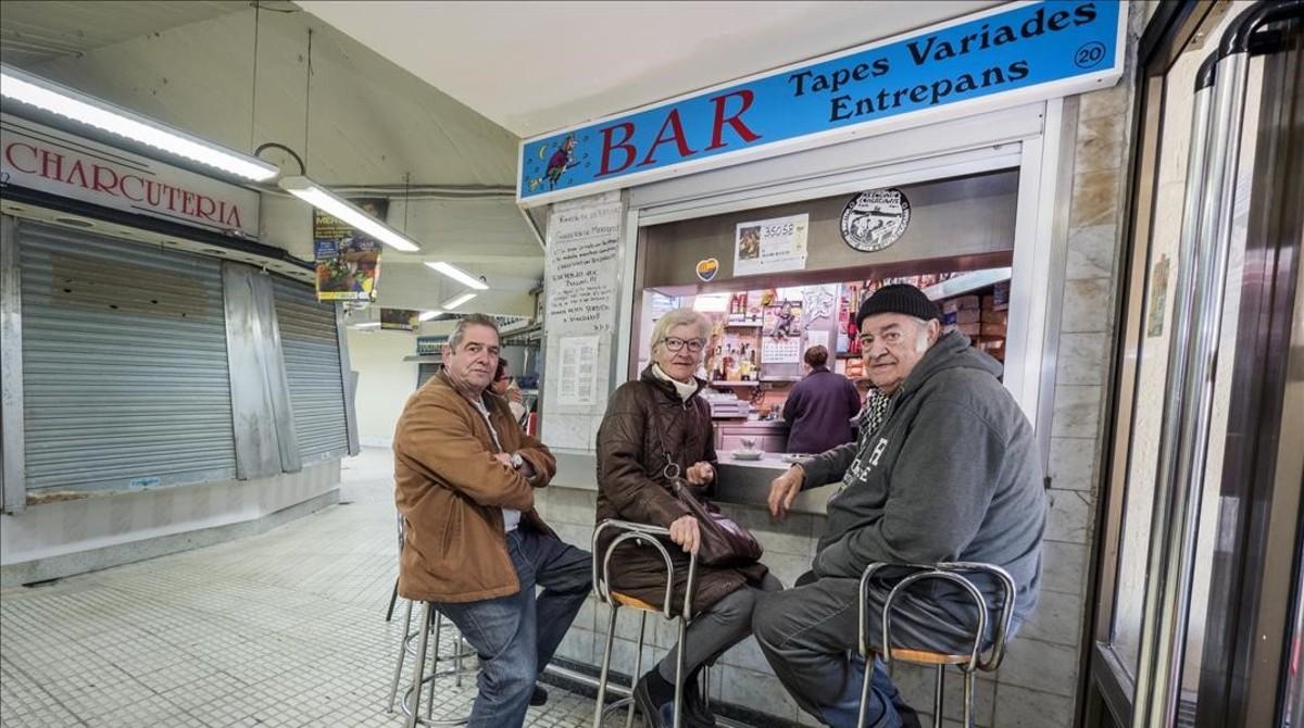 Clientela fija en el bar del mercado de Núria, a punto de cerrar.