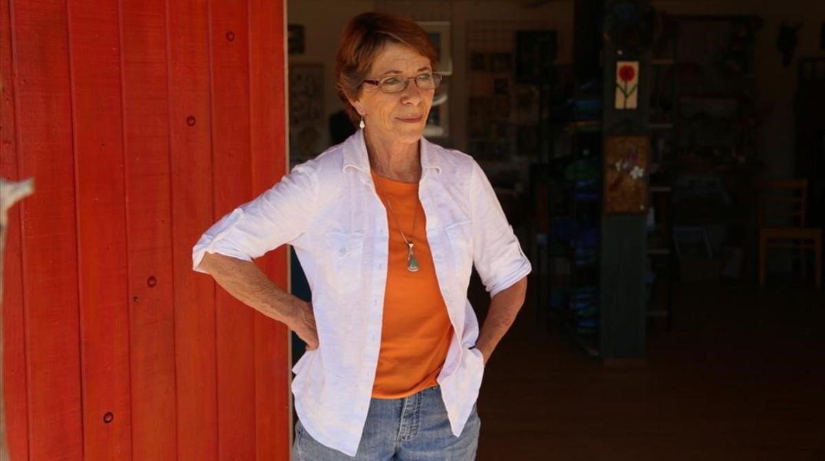 La artista Maggy Milinovitch posa junto a la cooperativa de artesanos que vende sus obras en Arivaca (Arizona).