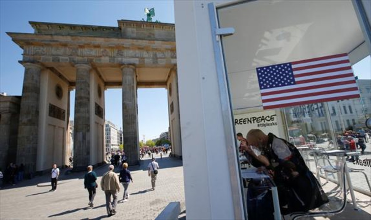 Ciudadanos consultan datos del TTIP, en una instalación de Greenpeace ante la puerta de Brandeburgo de Berlín, ayer.