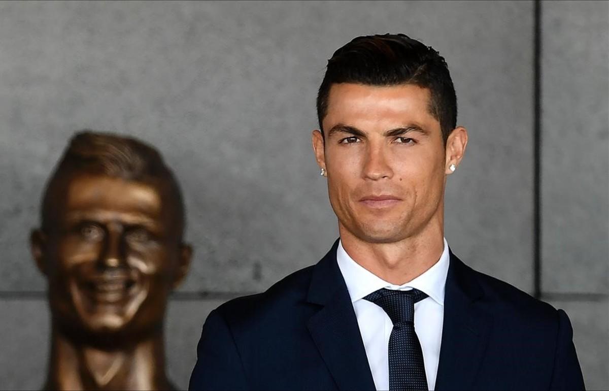 Cristiano Ronaldo, junto a su busto en Madeira.