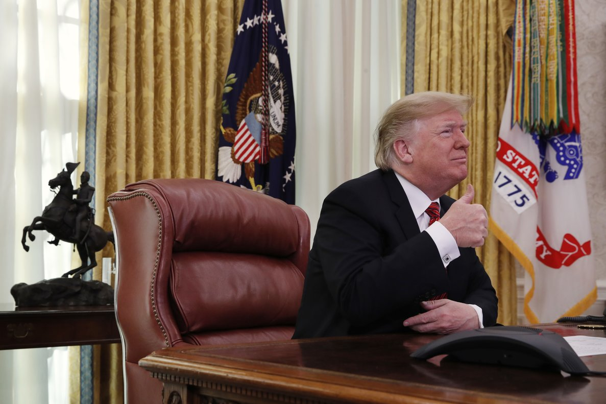 President Donald Trump gives the thumbs up sign while speaking with members of the five branches of the military by video conference on Christmas Day, Tuesday, Dec. 25, 2018, in the Oval Office of the White House. The military members were stationed in Guam, Qatar, Alaska, and two groups in Bahrain. (AP Photo/Jacquelyn Martin)