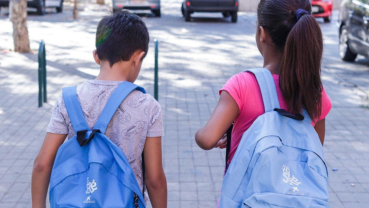 Dos niños que participan en el proyecto Chapotea, con las mochilas de CaixaProinfancia cargadas de material escolar.
