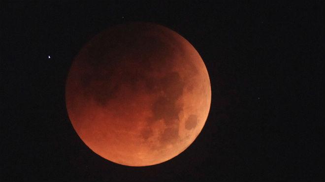 La lluna adquireix un característic color rogenc.