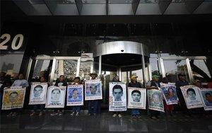 Padres y familiares con fotos de los estudiantes desaparecidos de Ayotzinapa.