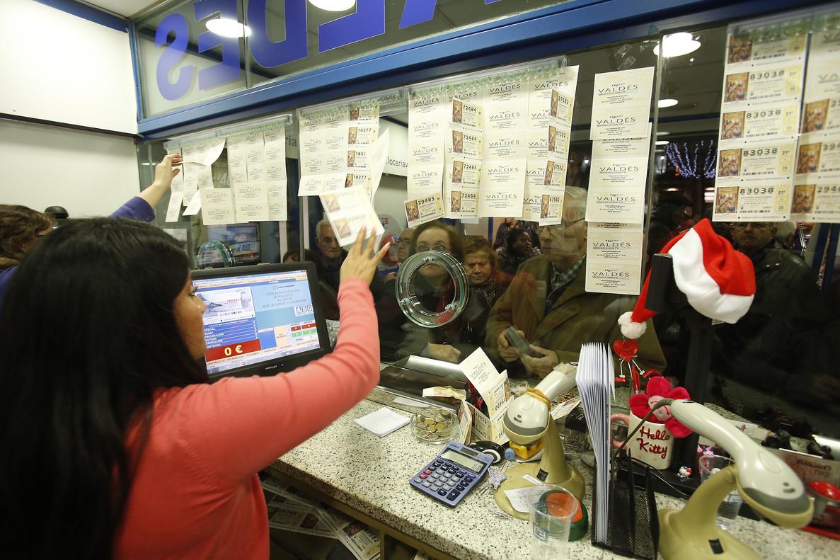 La gente se agolpa buscando la suerte en la Aministración Valdés, en la Rambla de Barcelona, un clásico navideño.