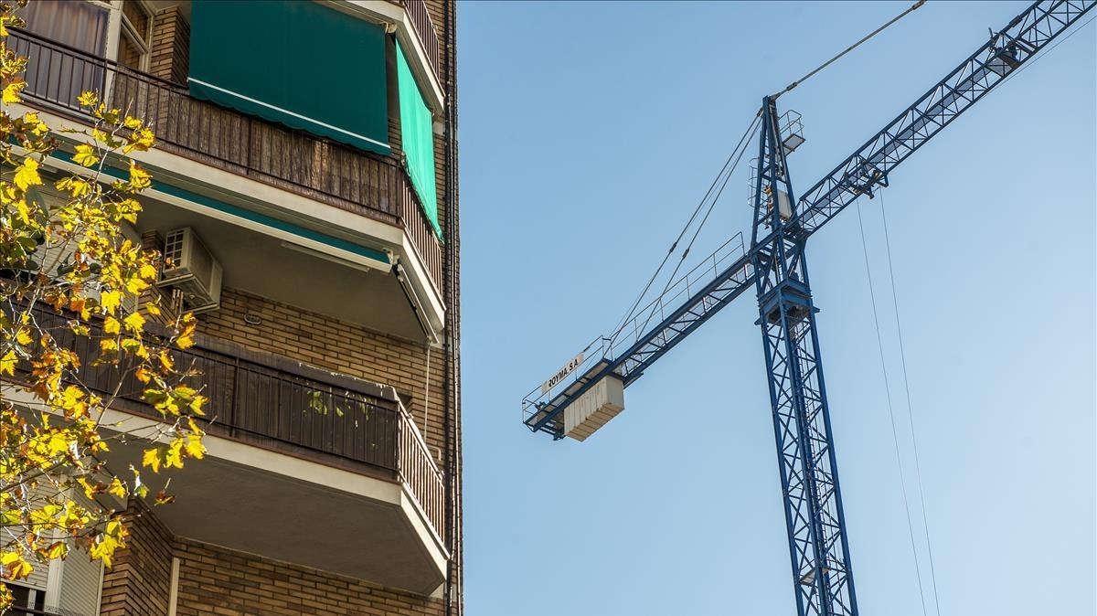Una grúa trabaja para rehabilitar edificios residenciales.