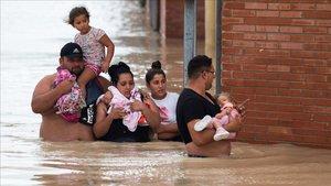 Un grupo de personas pone a salvo a sus bebés en Almoradi (Alicante).