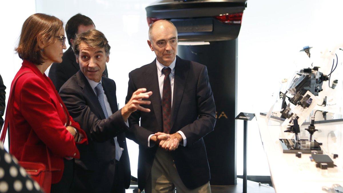 La ministra Reyes Maroto atiende las explicaciones del CEO de Ficosa, Javier Pujol.