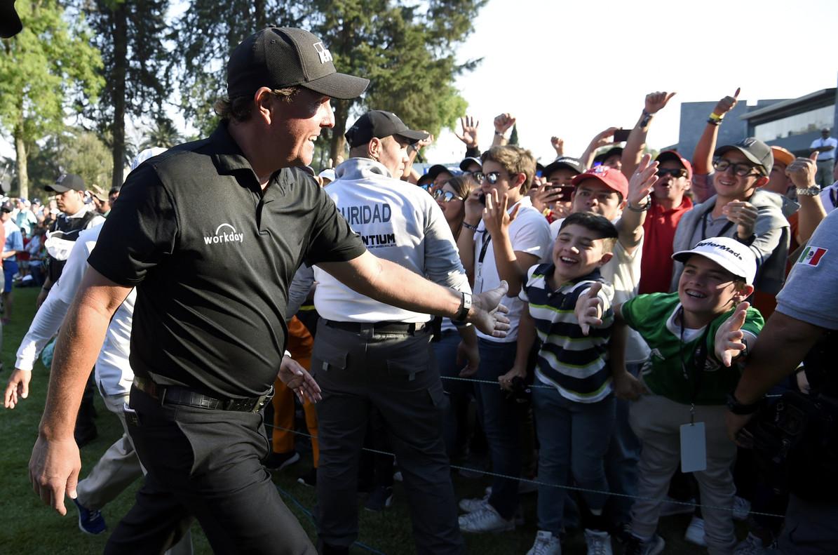 Mickelson saluda a unos niños a la salida del hoyo 18 en México DF