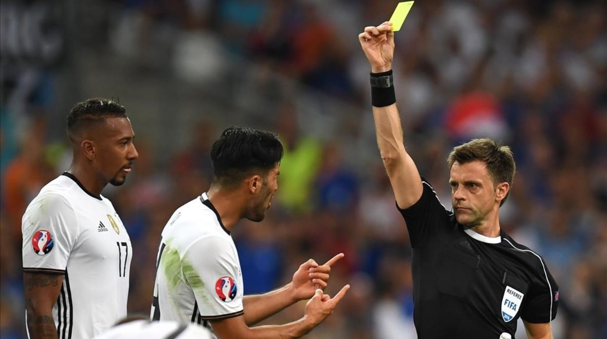 Nicola Rizzoli muestra la tarjeta amarilla a Emre Can ante Jerome Boateng.