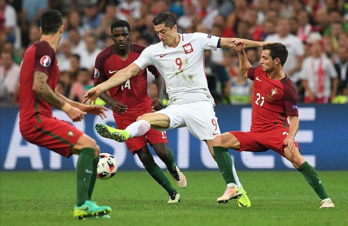 El polaco Lewandowski lucha el balón con los portugueses Carvalhoy Soares.