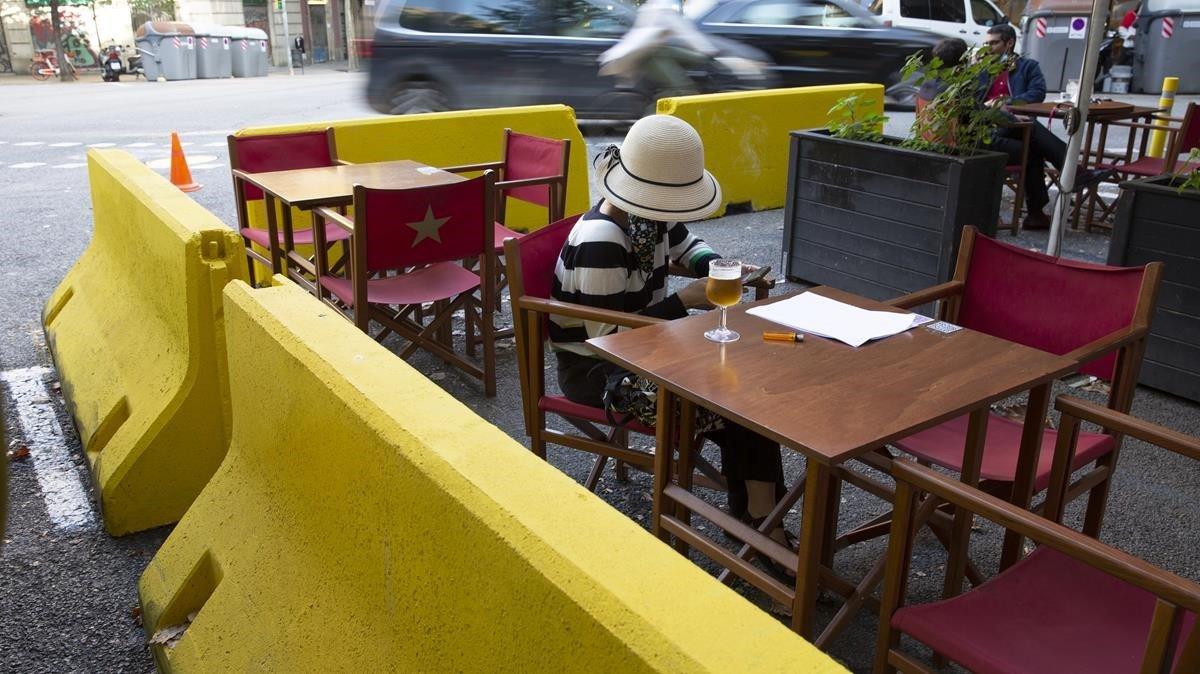Vallas de hormigón pintadas de amarillo separan el lugar de lectura en el Bar La Cremade la calle Diputacio 189 de la circulación de los coches, formando ya parte dela nueva normalidad provocada por el coronavirus