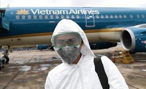 Un trabajador equipado con máscara para evitar el contagio por coronavirus se dispone a desinfectar un avión de Vietnam Airlines.