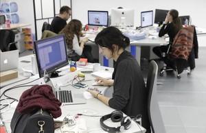 Trabajadores en una oficina frente al ordenador.
