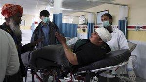 Una mujer herida en el ataque al templo sij de Kabul llega al hospital.