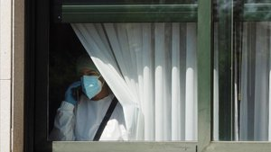 Una trabajadora sanitaria habla por teléfono este sábado desde el interior de la residencia de O Inicio (Lugo)